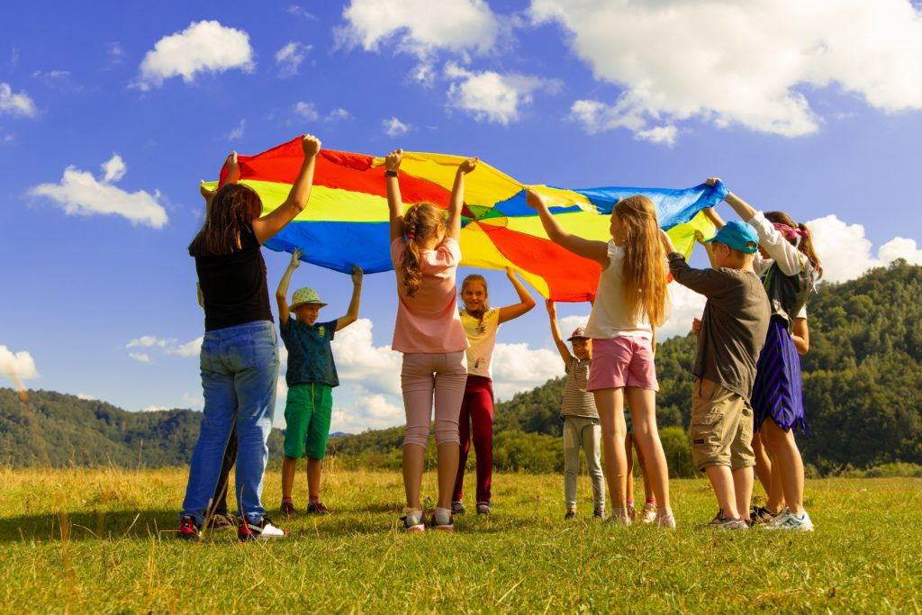Children playing together holding a sheet over their heads as a game