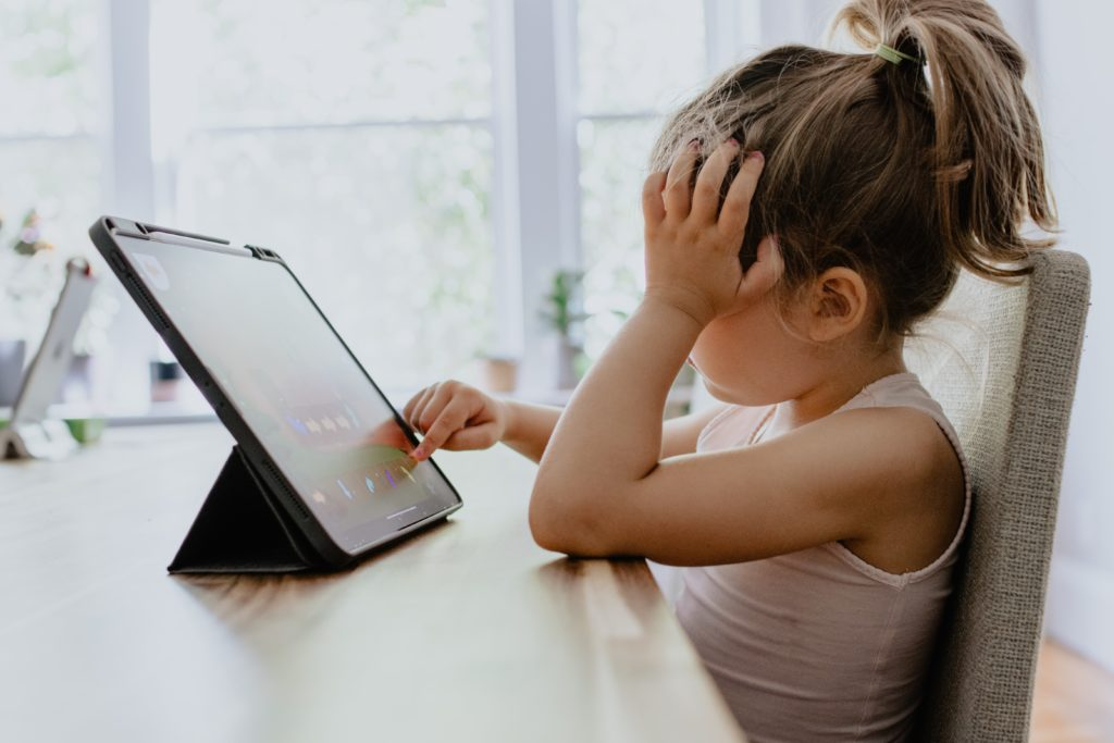 Girl sitting bored in front of a tablet