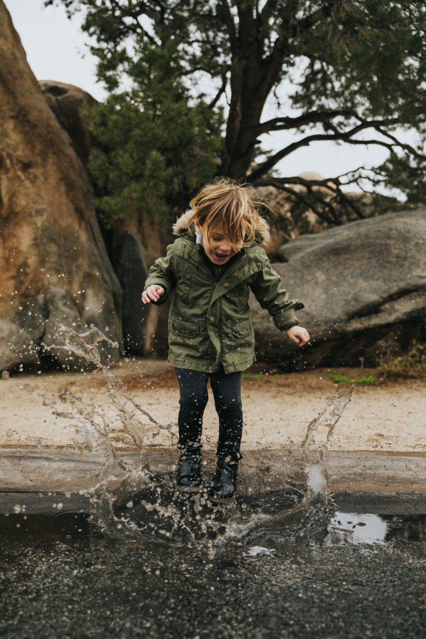 A child making a splash in a puddle of water